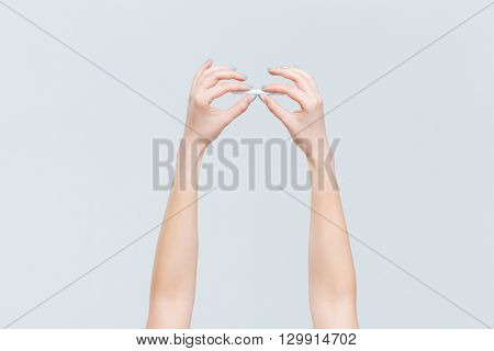 Female hands holding cigarette isolated on a white background