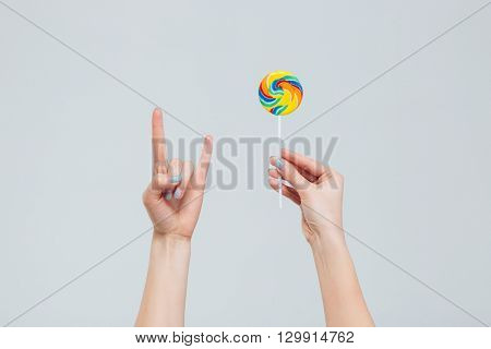 Female hands holding lollipop and showing devil sign isolated on a white background