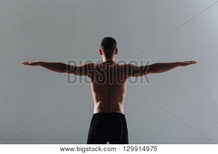 Back view portrait of a fitness man workout with arms at the sides over gray background