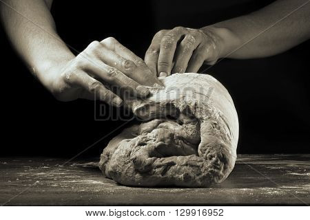 Women's hands knead the dough on a black background b/w
