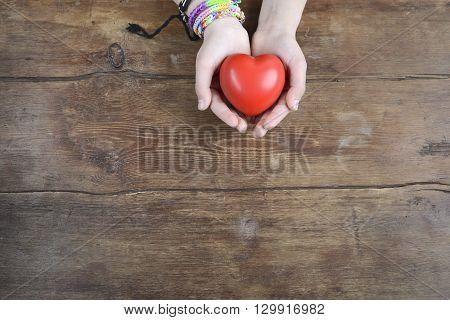 red heart in hands over vintage wooden background
