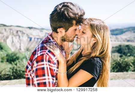 Couple passionated kiss. Young adults making trekking on the hills and sharing love emotions