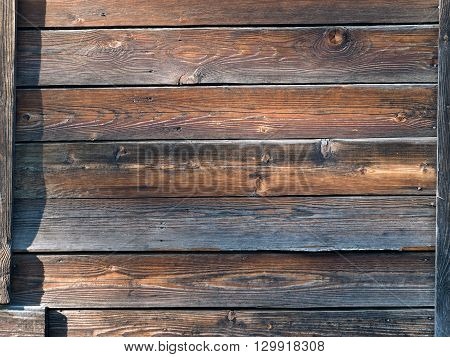 The wall of wooden village house. Old boards, sunlight. Texture of wooden boards.