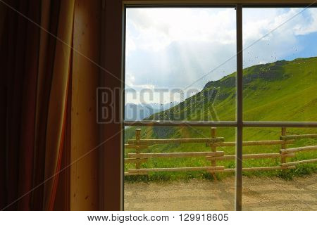 Rain starting on a mountain landscape, looking out the hut window