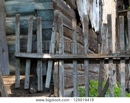 Old rustic picket fence in the sun. Behind the fence of the old wall, a wooden house