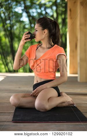 Beautiful girl sits on the black yoga mat on the wooden terrace on the nature background. Her head is turned to the right, legs are crossed, left hand lies on the legs. She drinks from the black cup in her right hand. She looks in front of herself. She we