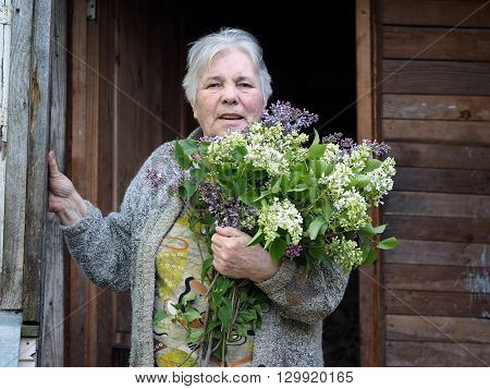 Old woman with a bouquet of lilacs. Portrait of a grandmother. Lots of gray hair, wrinkles. The old woman on the threshold of the old village house