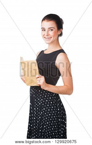 Smiling pretty girl in elegant dress standing with the opened book, isolated on white background