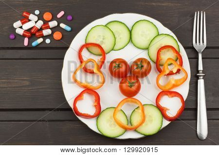 Diet and supplements on a wooden table. Strict diet meals. Slimming diet. Tomatoes and pills.