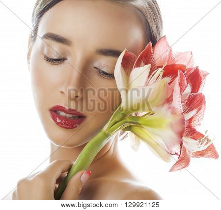 young pretty brunette woman with red flower amaryllis close up isolated on white background. Fancy fashion makeup, bright lipstick, creative Ombre manicured nails. spa skin care