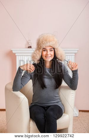 Beautiful girl in white fur hat hat with ear flaps are sitting in armchair near fireplace