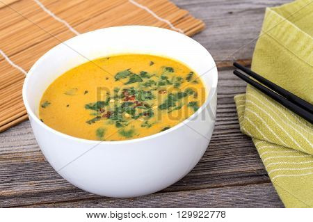 thai yellow curry soup with cilantro on rustic table