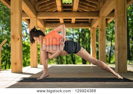 Young girl makes low lunge with left leg forward on the black yoga mat on the wooden terrace on the nature background. She holds her hands together on her back and left hand is clasping left leg. She looks at the floor with parted lips. She wears orange t
