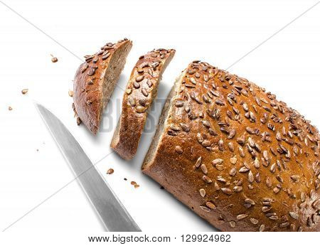 Cut loaf of wholemeal bread and knife isolated on white background as a healthy eating concept.
