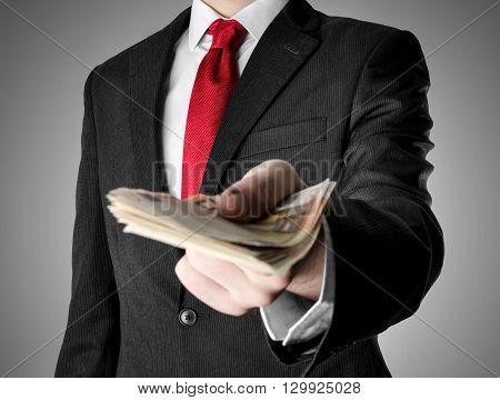 Businessman with red tie giving fifty euro notes.