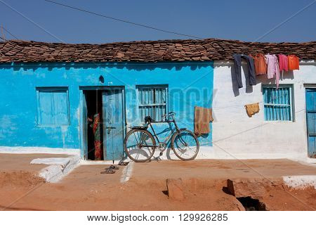 ORCHHA, INDIA - DEC 23, 2012: Traditional indian house of blue color with a woman standing in the doorway on December 23, 2012 in Orchha India. Town Orchha in Madhya Pradesh state has a population of 10000