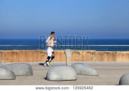 TEL AVIV, ISRAEL - APRIL 1, 2016: People run on promenade in Tel Aviv port, Israel. Selective focus.