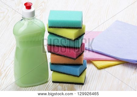 sponges, rsgs and a bottle of detergent on wooden background