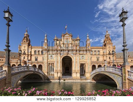 Seville, Spain - April 30, 2016: Central part of the pavilion at Plaza de Espana, view from between the two bridges. Tourists visiting the famous square.