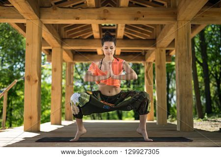 Cute girl does sumo squats on the black yoga mat on the wooden terrace on the nature background. She stands on the toes and holds her palms  together. She looks at the floor with parted lips. She wears orange t-shirt and the wide olive pants with images.