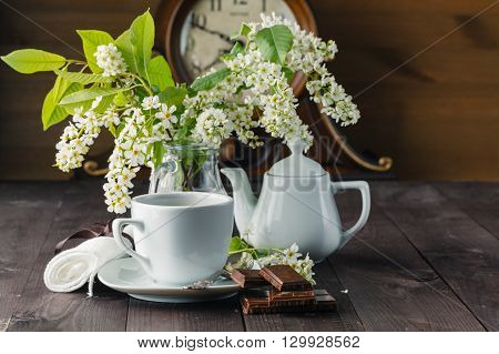 Kettle and cups with spring flowers on wooden table