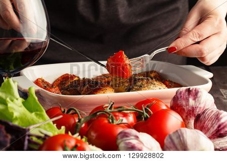 Woman get roasted chicken aтв tomato from bowl