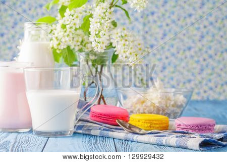 Glass of milk with french macaroon and spring flowers