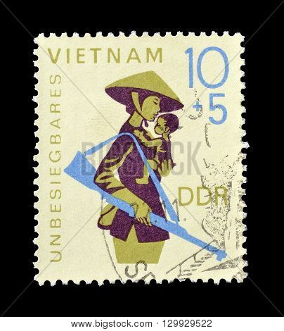 GERMAN DEMOCRATIC REPUBLIC - CIRCA 1968 : Cancelled postage stamp printed by German Democratic Republic, that shows Armed mother and child in Vietnam.
