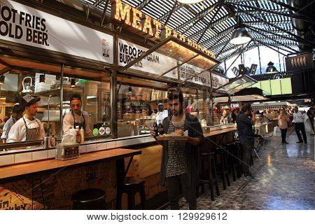 TEL AVIV, ISRAEL - APRIL 7, 2016 : People having lunch in a modern open kitchen restaurant in Sarona Market, Tel Aviv, Israel. Recently open Sarona Market became the most popular place in Tel Aviv.