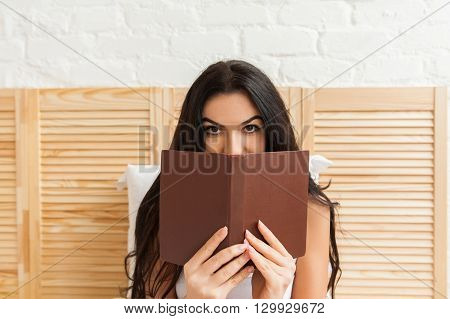 Beautiful girl hiding her face behind the book