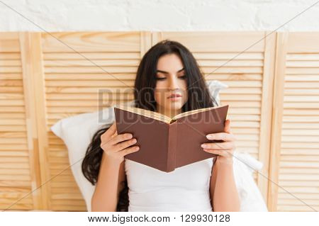 Portrait of a beautiful woman reading a book in bed