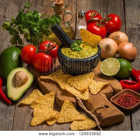 Bowl of delicious homemade Guacamole with nachos next to fresh ingredients on wooden background