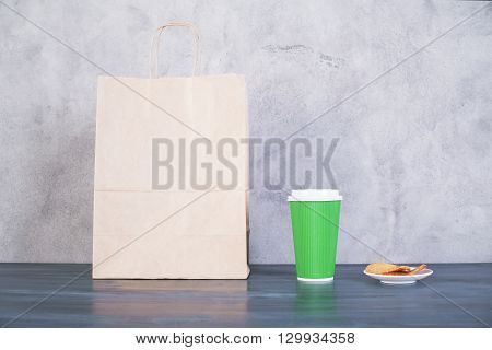 Front view of blank take away food bag cookies on saucer and green coffee cup on wooden surface and concrete background. Mock up
