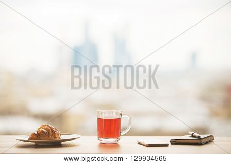 Tabletop with cup of tea croissant on plate phone and notepad on blurry city background