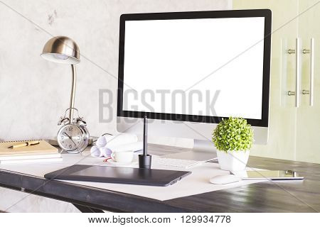 Sideview of designer desktop with blank white computer screen graphic tablet alarm clock and other items. Concrete wall and glass door in the background. Mock up