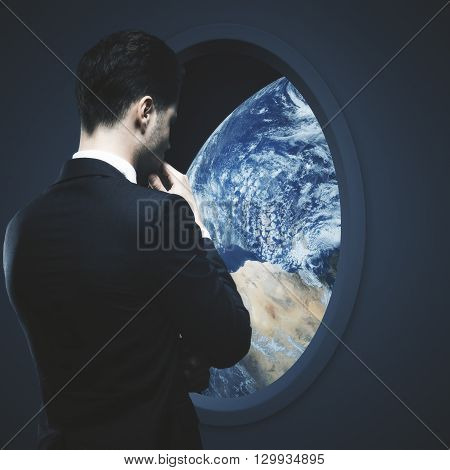 Thoughtful businessman looking at earth outside dark spaceship window.
