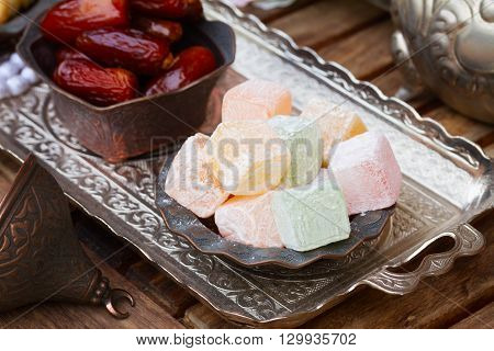 Lumps of Lokum or Turkish Delight close up  in a tradition copper vase on oriental  metal tray