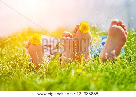 Kids feet with dandelion flowers lying on green grass in sunny day. Concept happy chidlhood.