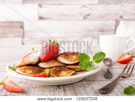 Dutch mini pancakes called poffertjes with strawberries and mint, sprinkled with powdered sugar. Healthy food concept with copy space.