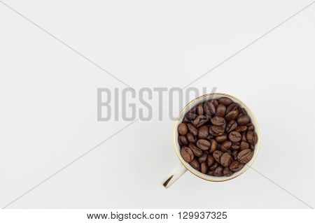 Freshly roasted coffee beans, packed in a cup. We like strong coffee. Sales of fresh coffee. Advertising on a cafe.