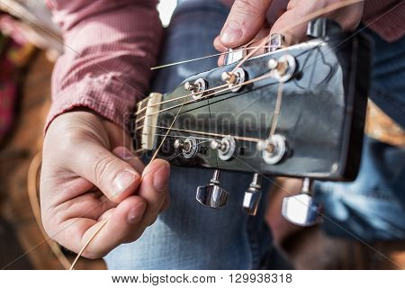 a man in a plaid shirt pulls in new guitar strings acoustic guitar close-up