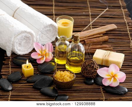 frangipani with towel,oil ,soap ,stones on bamboo mat