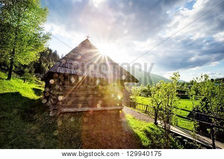 Wooden house in middle of lawn at sunset in mountains Carpathians