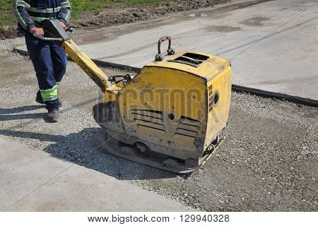 Worker Use Vibratory Plate Compactor At Road Construction Site