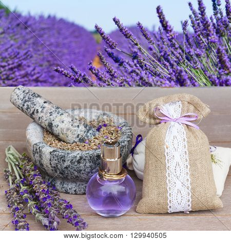 Lavender herbal water in a glass bottle with fresh and dry flowers on  wooden table, lavender field in background
