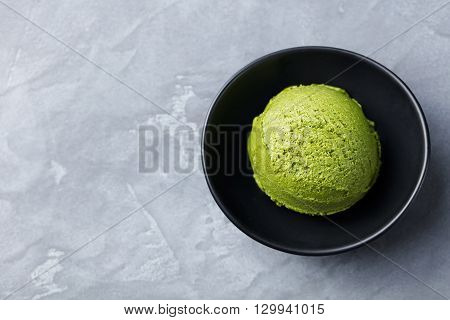 Green tea matcha ice cream scoop in black bowl on a grey stone background. Copy space. Top view