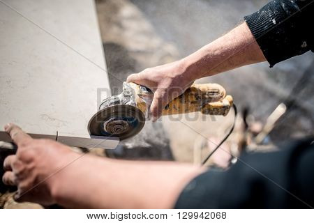 Worker At Construction Site Using Grinder For Cutting Slate