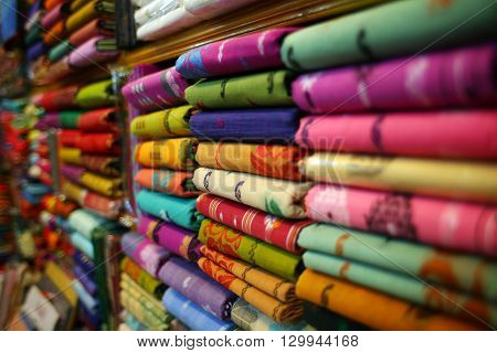shopping, industry, sale and clothing concept - colorful textile at asian market