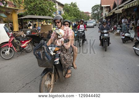 Siem Reap, Cambodia - MAY 04, 2016: A family of three on a motor bike going through the streets of Siem