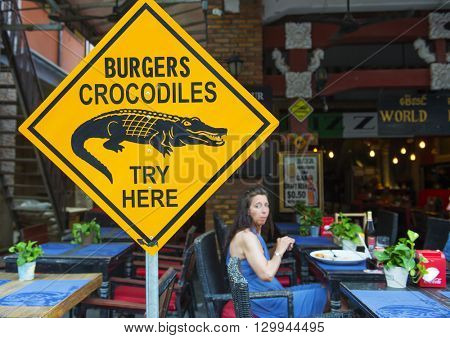 Siem Reap, Cambodia - MAY 04, 2016: An unknown woman in a cafe, which serves burgers from a crocodile.